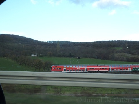Red train running along the motorway. Germany